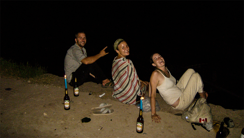 Three people enjoy beer in the dark in Laos