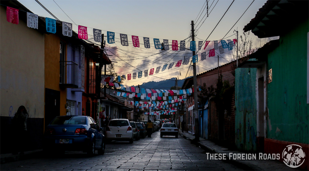 An dark street with flags above the road, just after sunset.