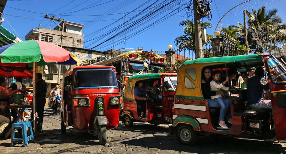 Small, three wheeled moto-taxis on a busy street in Panahachel Lake Atitlan