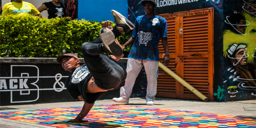Comuna 13 Colombia: A break-dancer preforms on the side of the road