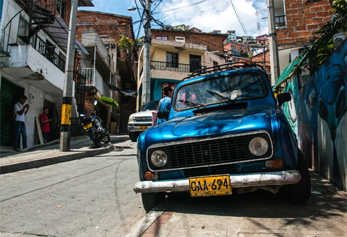 Comuna 13 Colombia: A blue car parked on the side of the road
