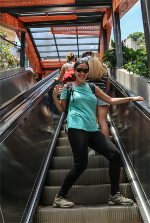 Medellin Colombia: Kylee riding one of the escalators of Comuna 13