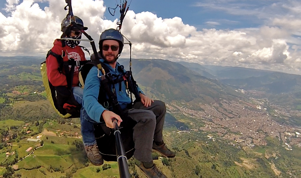 Two people hanging from a harness high above Medellin