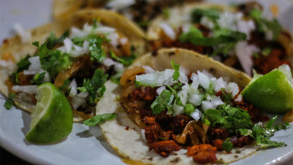 Tacos topped with cilantro and onions.