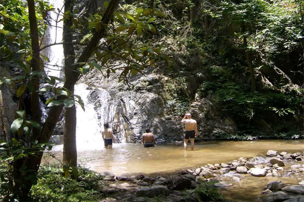 Three men stand in a waterfall