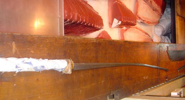 A very long, sword-like knife sits beside some tuna