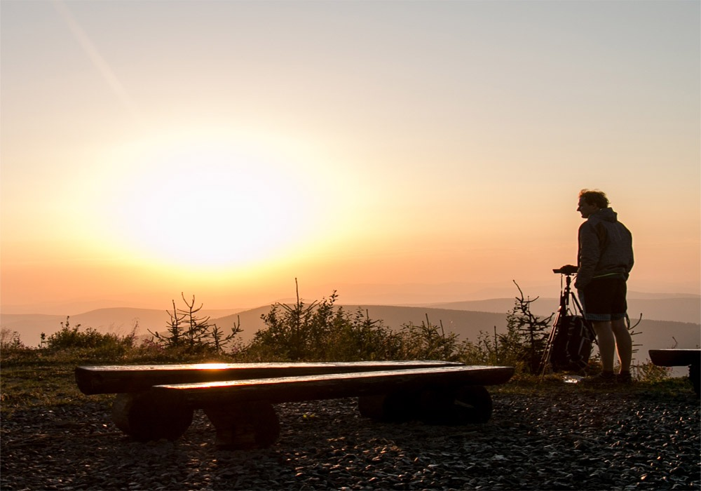 A photographer stands looking at the sunrise from Lysa Hora