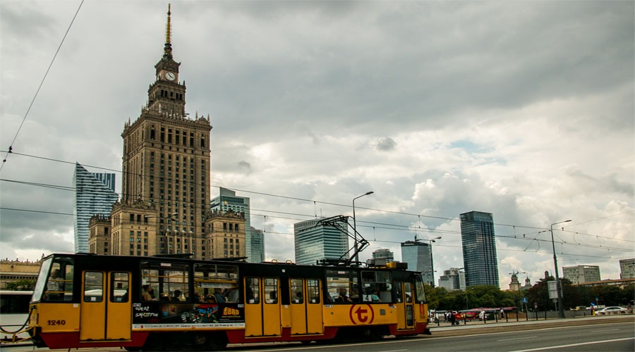 A yellow and red tram passes in front of a large, concrete skyscraper