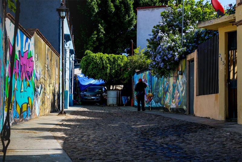 A cobblestone alley with colourful graffiti on the walls