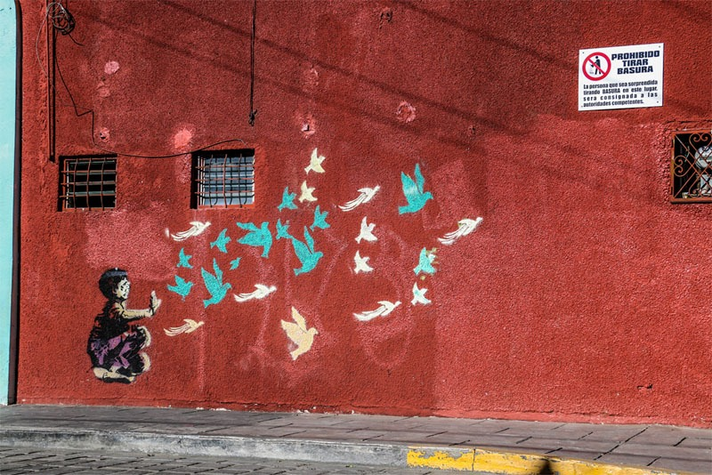 A red wall with graffiti of a child releasing birds