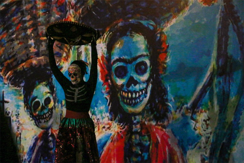 A girl in traditional makeup dancing against a skeleton background