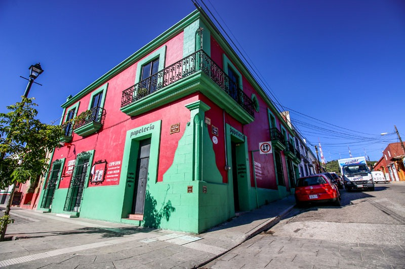A bright pink and green building on a street corner