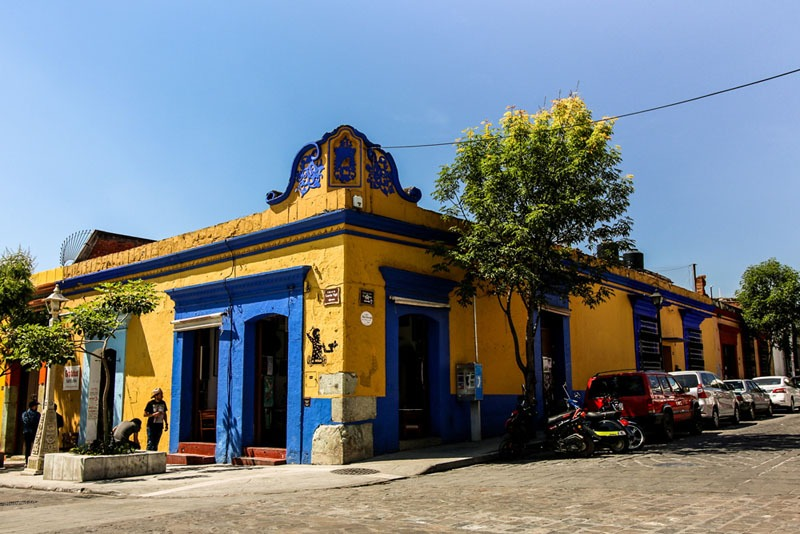 A bright blue and yellow building on a street corner