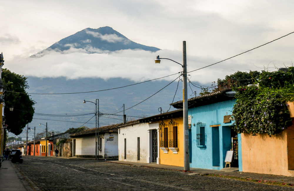 A row of colourful concrete houses along a stone road, with a volcano in the distance