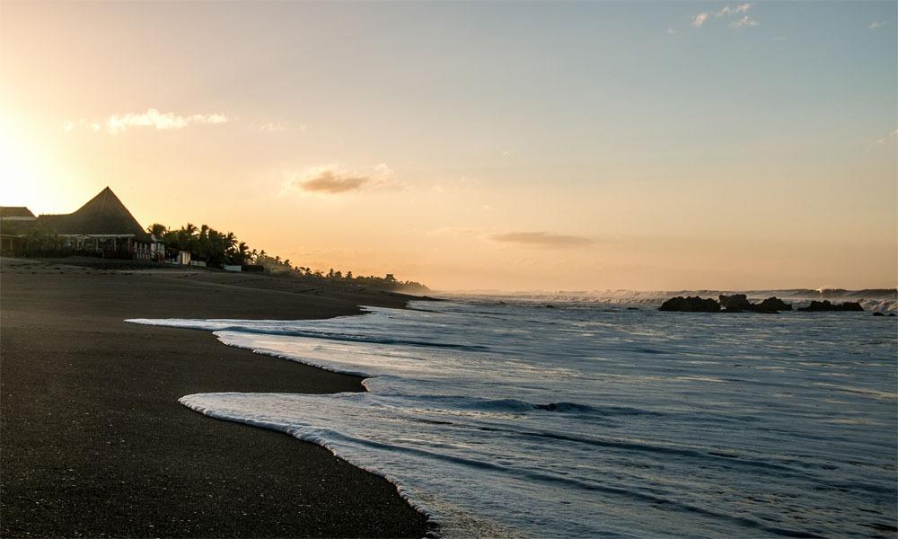 Sunrise over a sandy beach as waves crash onto the shore