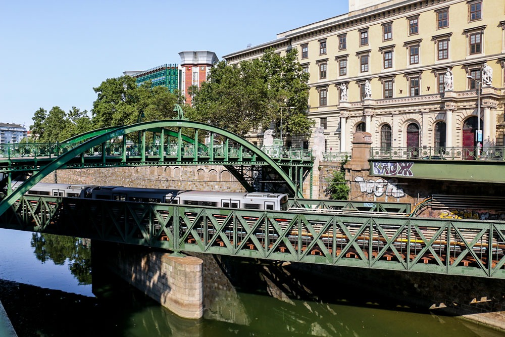A pedestrian bridge crosses over a subway bridge over a canal in Vienna