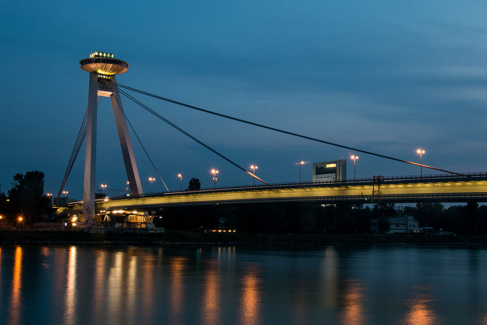 A one-pillared suspension bridge over the Danube river at night