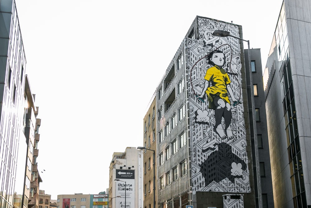A large painting on the side of a building of a girl in a yellow dress skipping roap