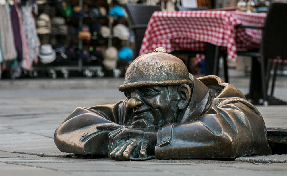 Statue of a working man inside of a manhole in Bratislava