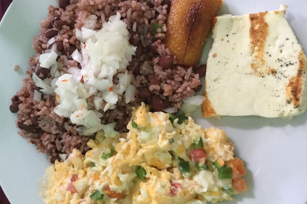 A plate of rice, beans, salsa, plantain and eggs. Free breakfast is a great way to save money while travelling.