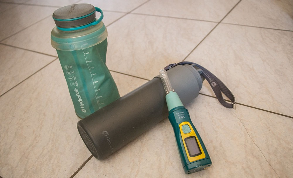 Two different collapsible water bottles and an electronic water purifying wand