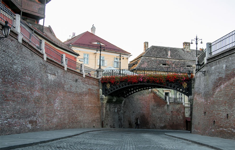 A foot bridge over a cobblestone street