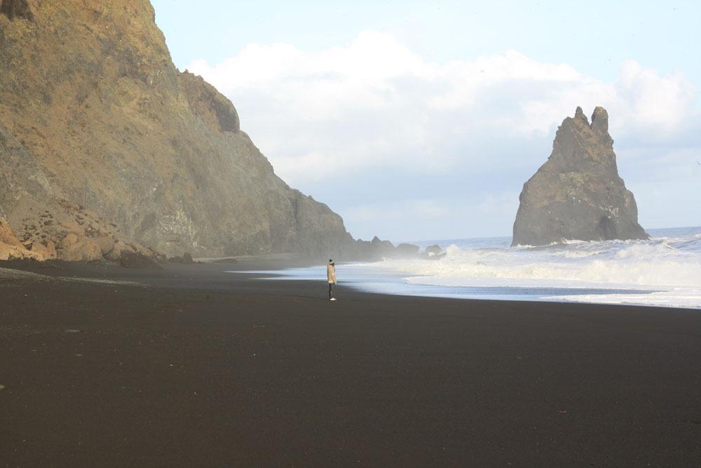 A girl on a black sand beach in