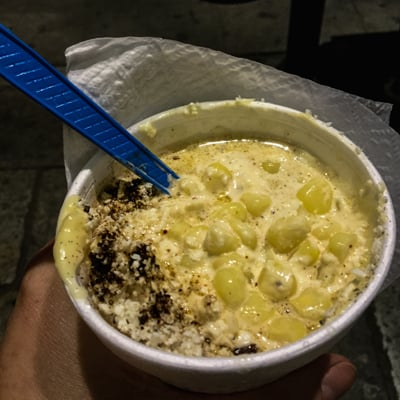 Styrofoam cup filled with corn and sauces, one of the best cheap eats in Oaxaca