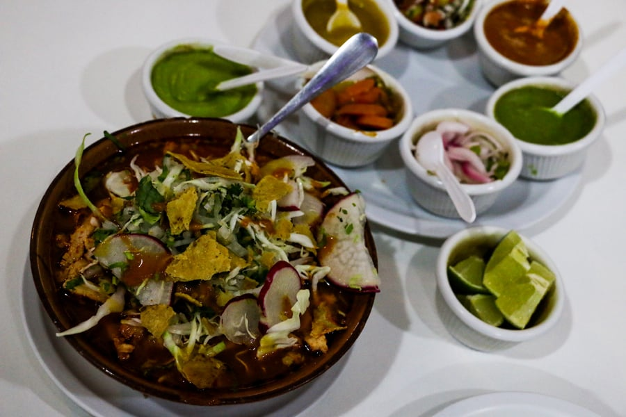A soup in Oaxaca with a plate full of condiments
