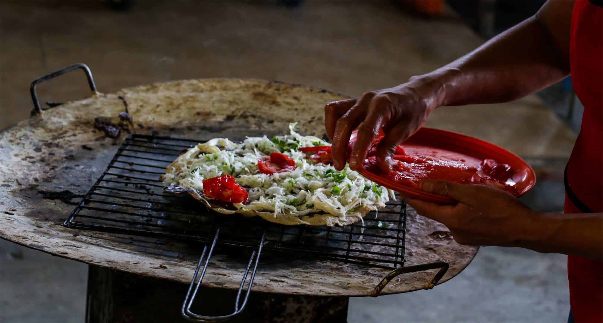A tlayuda being prepared over charcoal. While maybe not the best food in Oaxaca, it's close!