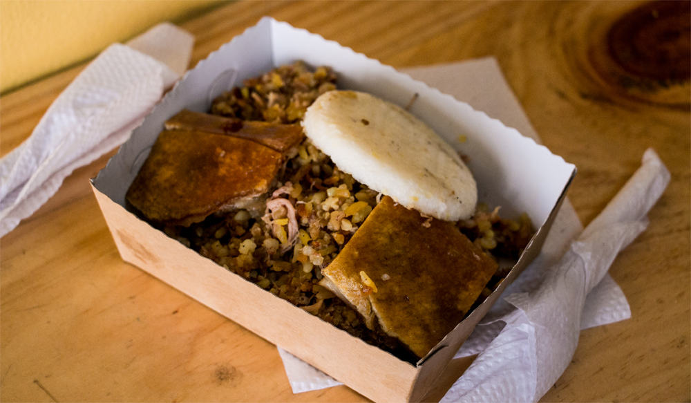 A small cardboard tray filled with meat and rice. Two pieces of crispy pig skin are on top.