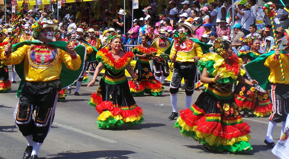 People in colourful clothing dance in the street