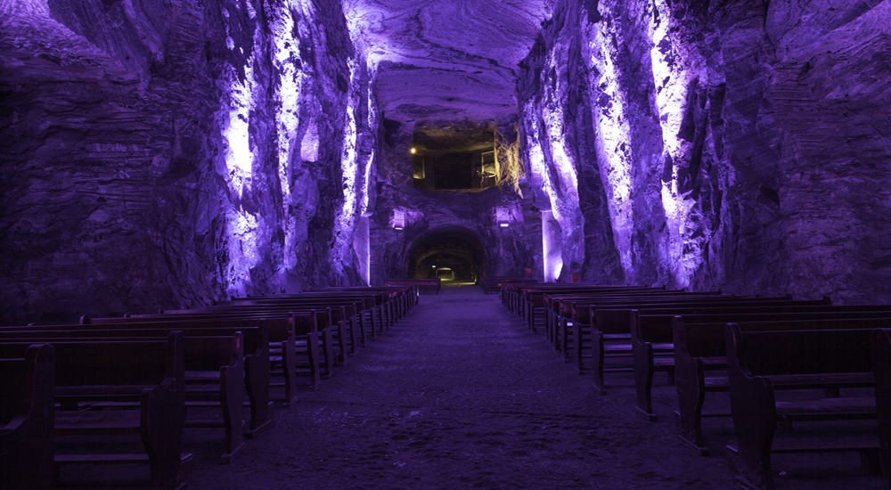 Church pews under a purple light, deep underground. A cross stands in the background.