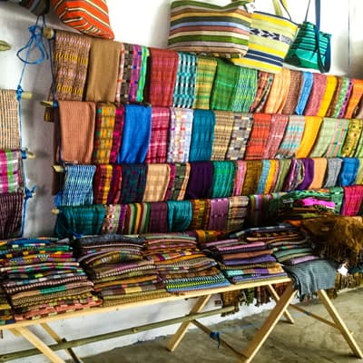 Traditional hand-woven Mayan fabrics, hanging on a wall display.