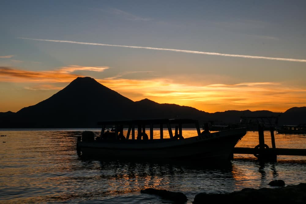 Sunset over Lake Atitlan with boat in foreground, volcano in the back.