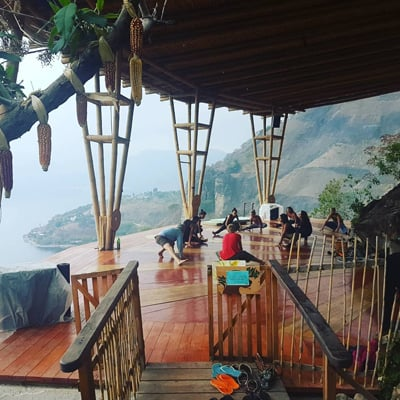Several people doing yoga on a platform high above Lake Atitlan