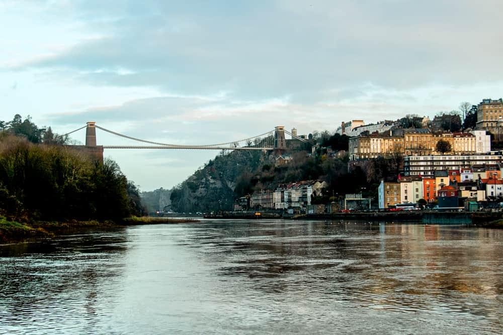 A river passing under a bridge through a wide gorge in Bristol