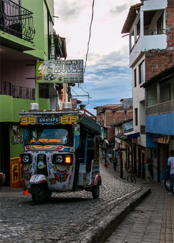 A colourful tuk-tuk driving along a small road