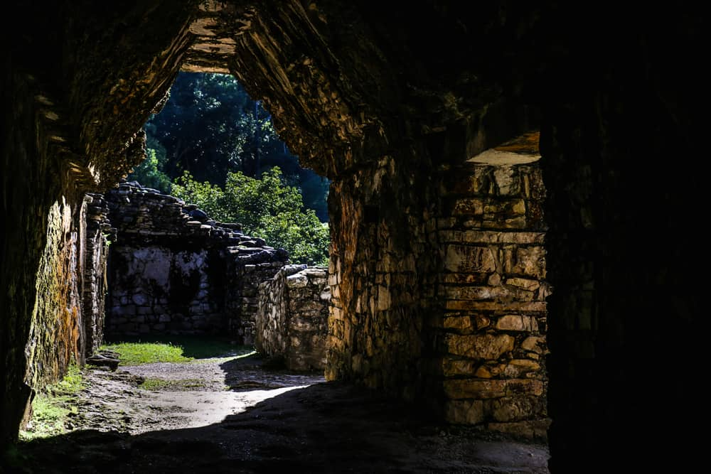 a dark tunnel inside the Palace of Paleque, light is coming in from the crumbled ceiling