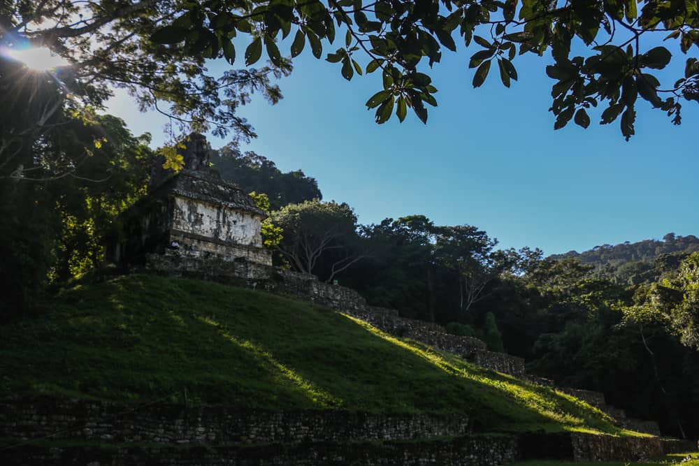 The Temple of the cross in Palenque with sun shining through the trees