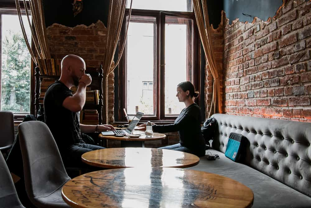 Two people sitting in a cafe using the fast internet in Romania