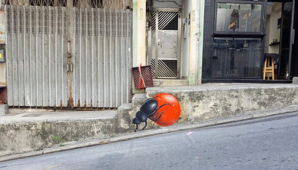 Graffiti of a beetle rolling a red ball on the curb