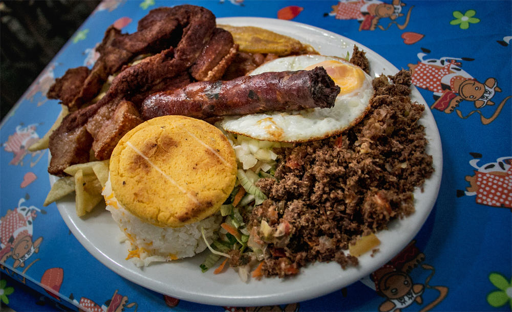 A plate topped with several types of meat, an egg, and rice.