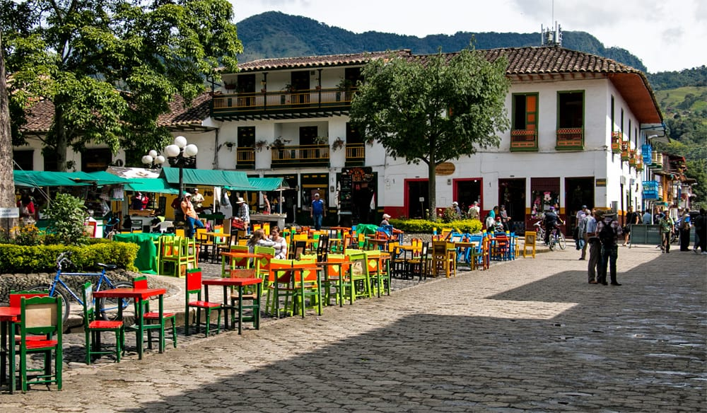 Colourful tables and chairs surrounded by trees. Colourful buildings surround the square