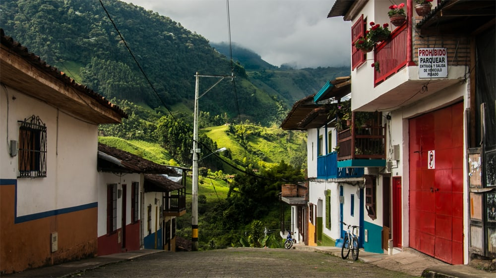 Colourful houses on a street that leads into a green valley