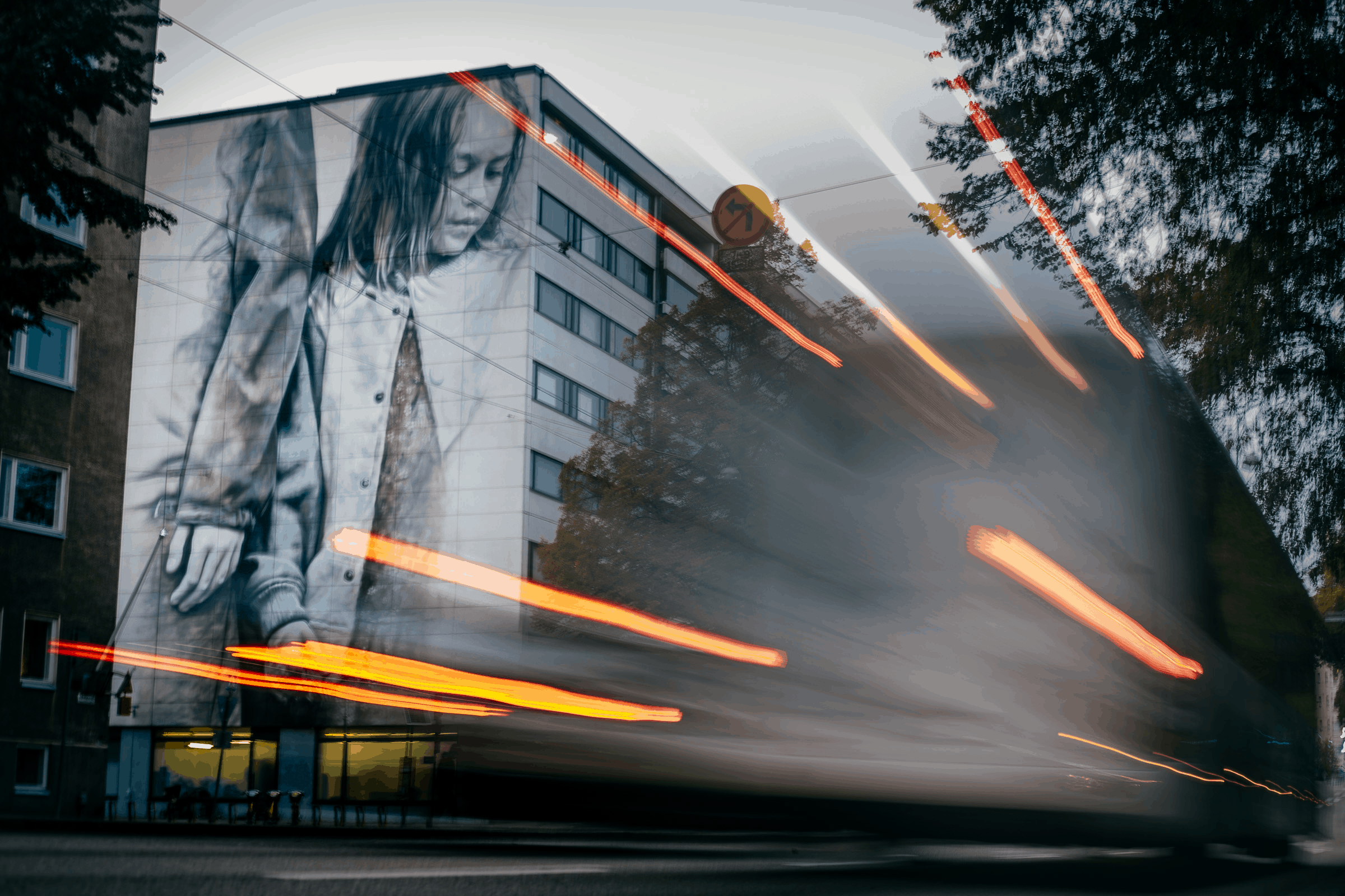 Lights of a vehicle pass a multi-story painting of a young girl on an apartment wall