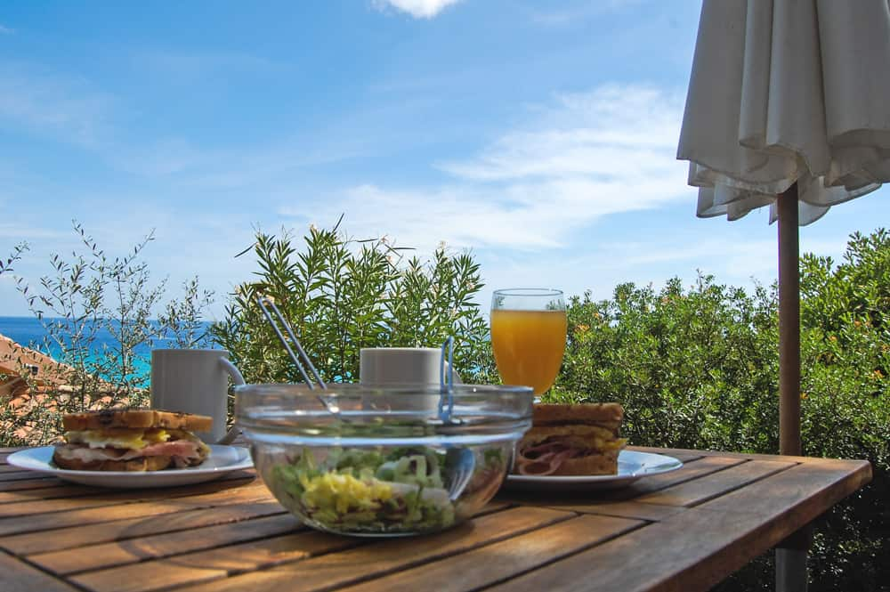 A table with a bowl of salad and a glass of juice overlooking the ocean