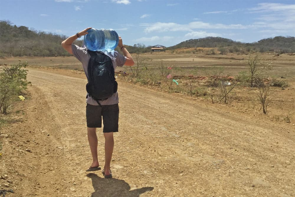 Mark walking down a dusty road with a water bottle on his shoulder