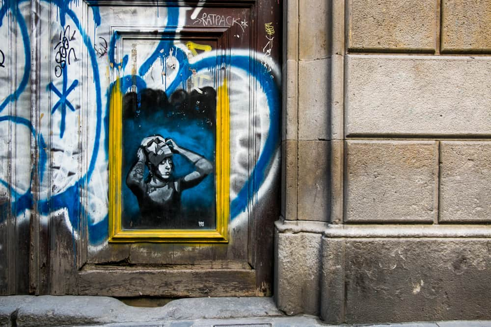 Barcelona street art of a girl taking off a mask