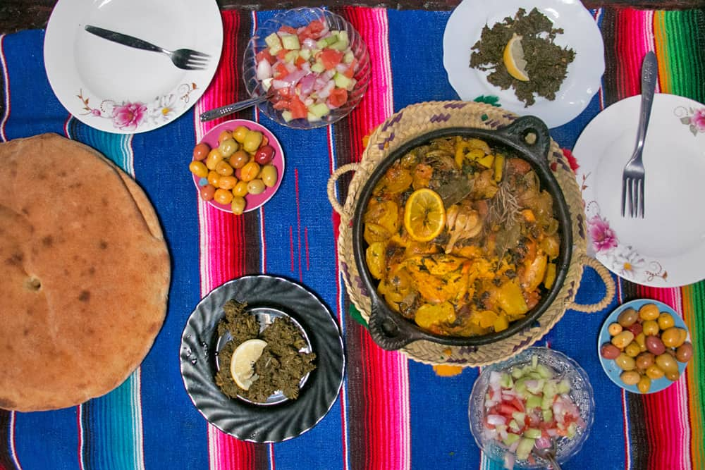 Several plates with different food including olives, bread and a chicken tagine in Morocco
